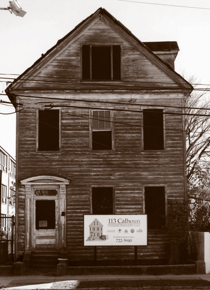 A rundown house with a development sign in front.