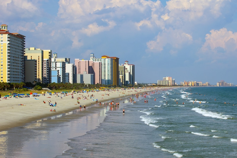 The highly developed shore of Myrtle Beach, South Carolina, showing tall buildings and many people.