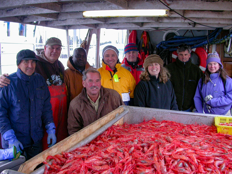 A group of people in warm clothing stands in front of a bin of shrimp.