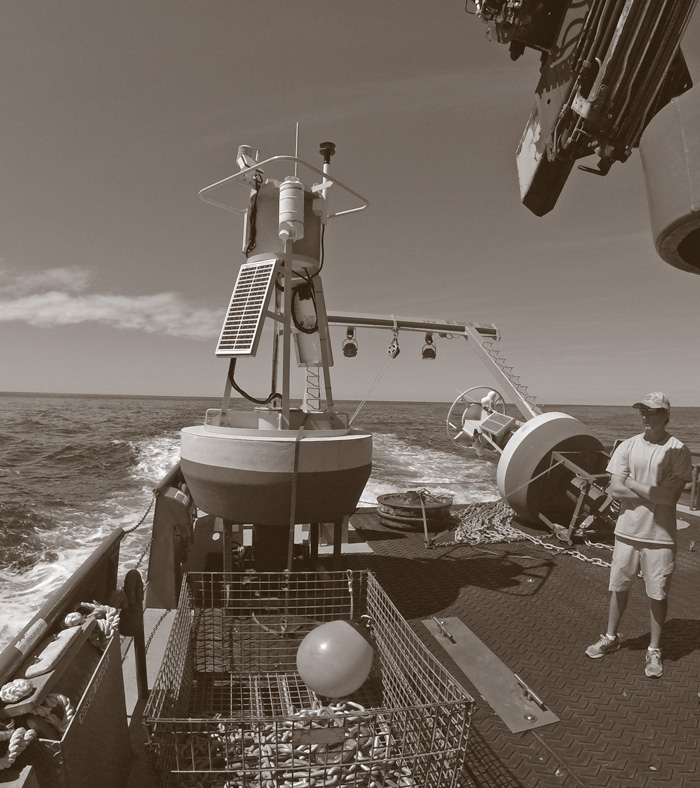 A buoy with sensors sits on a boat in the water, while a crewmember looks on.