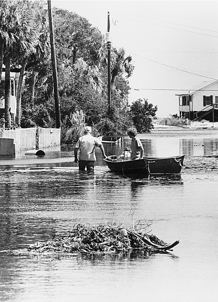 Residents use a boat to navigate a flooded urban area.