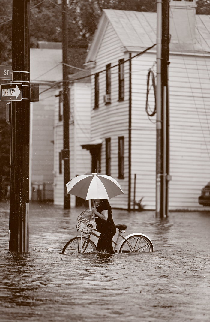A woman pushes a bike through a flooded street.