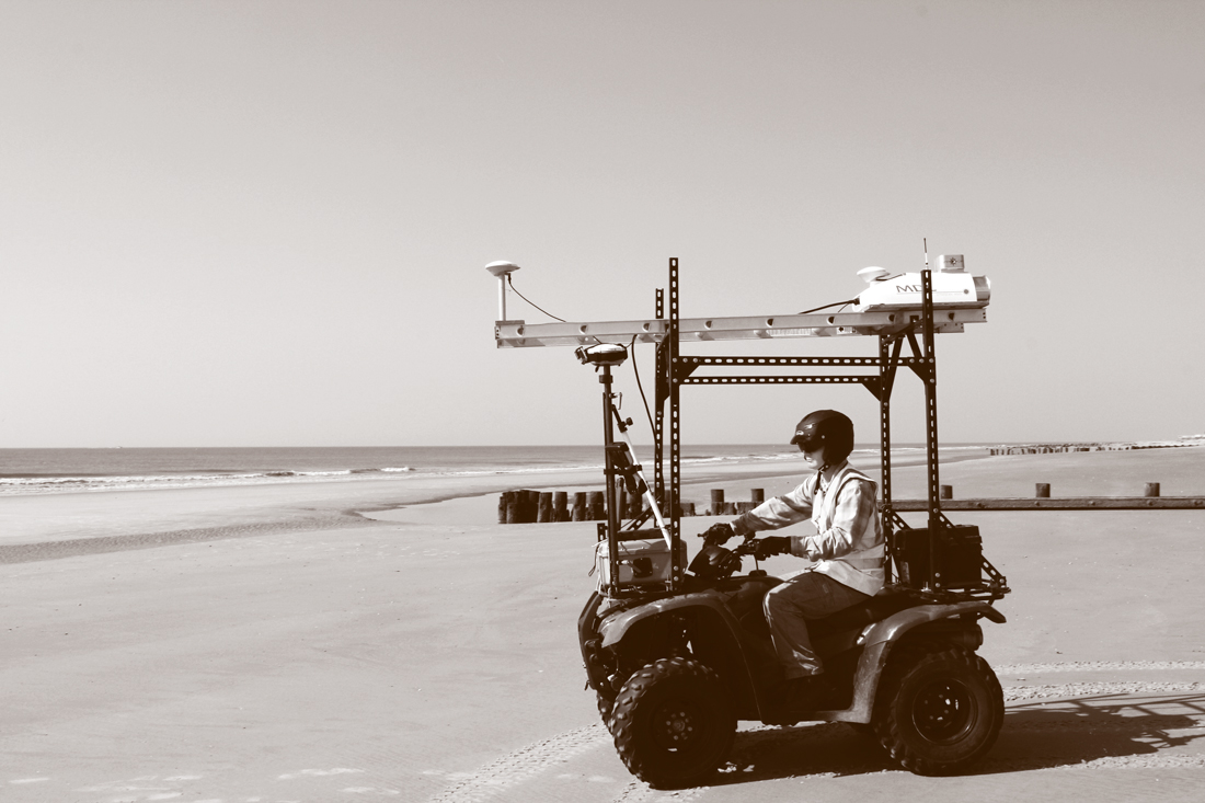 A person operating an all-terrain vehicle on a beach.