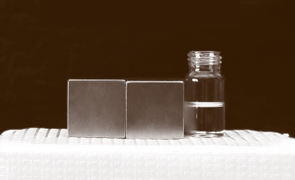 Two large magnets next to a jar of water.