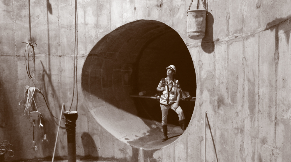 A worker inside a large pipe.