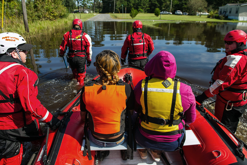 A group of people in life jackets and safety equipment navigate a boat through a flooded neighborhood.