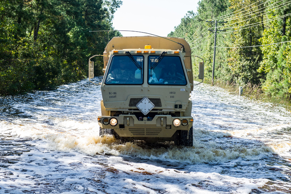A military-style vehicle drives through a deeply flooded roadway.