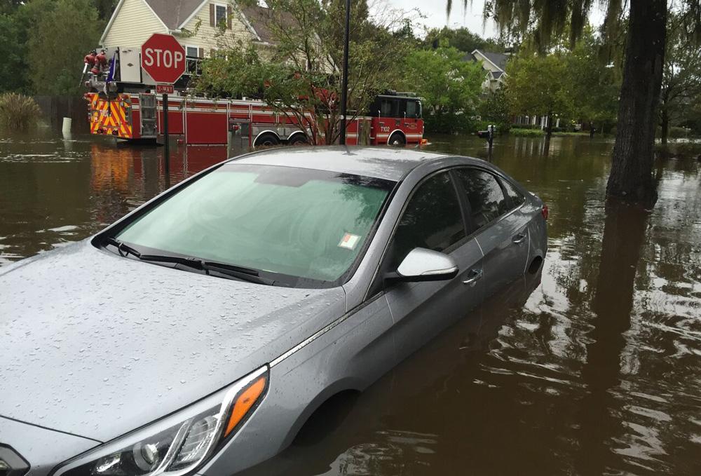 A car in a flooded Charleston street.