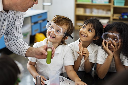 Children doing a science experiment in a classroom.