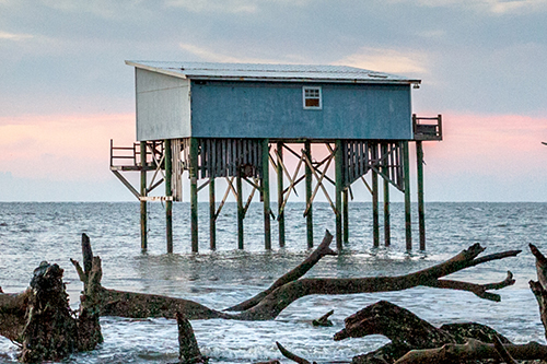 An old beach house that once stood on the shore is now in the water.