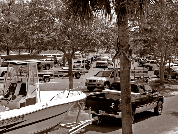 A crowded boat landing parking lot with many cars.