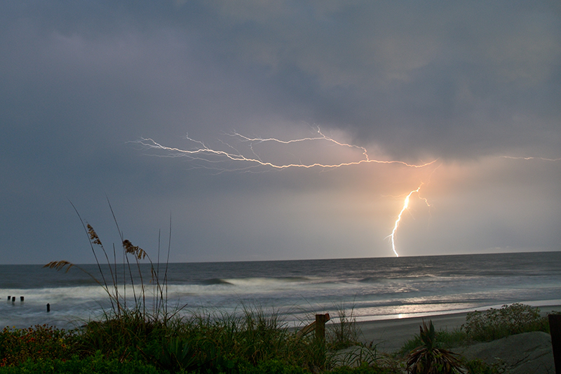 Lightning strikes the water from dark with stormclouds at Folly Beach, South Carolina.