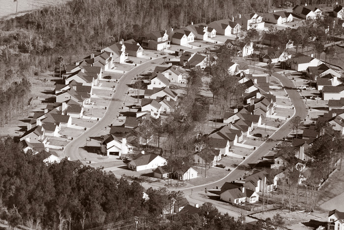 An aerial view of a housing development, showing dozens of uniformly built houses.