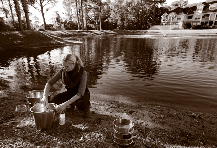 A researcher takes water samples from a stormwater pond.