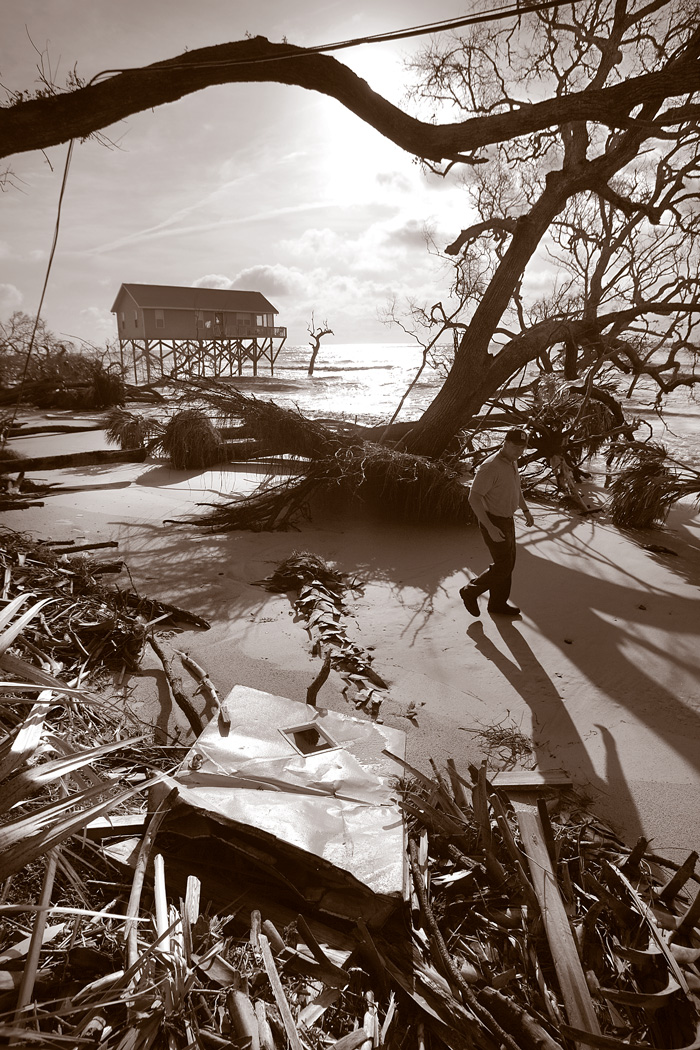 A person walks along the sand on a beach with a dead and uprooted tree, many pieces of debris washed up, and an abandoned beach now standing in the water.