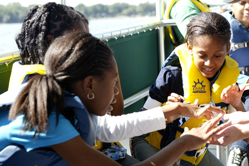 Several young students in life jackets examine marine life.