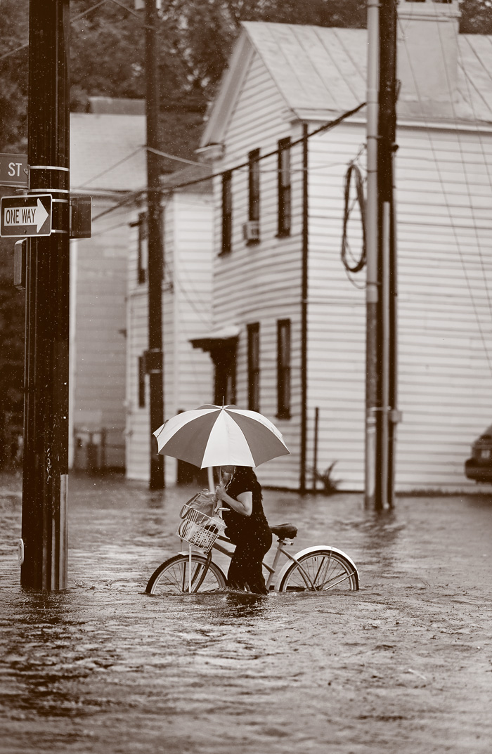A person with a large umbrella walks a bike through a deep flood.